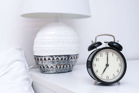 An alarm clock showing 7 oclock in the morning on a bedside table with lamp.