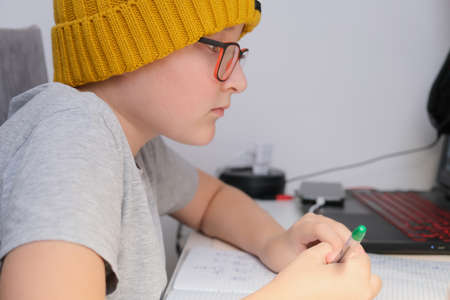 A boy in a trendy yellow knitted hat sitting by the table at home and doing homework, he using a laptop and whiting in a notebook. Reklamní fotografie
