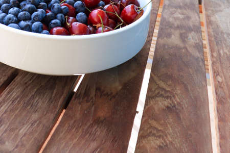 Raw juicy berries of sweet cherry and blueberry in a white ceramic dish on wooden table, copy space. Reklamní fotografie