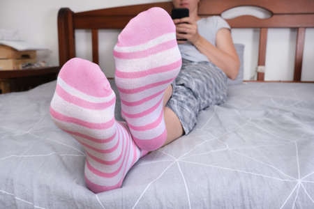 Crossed feet in cozy cotton striped pink and white socks of a woman sitting on a bed and relaxing while using smartphone, serfing internet in the evening