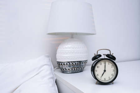 An alarm clock showing 7 oclock in the morning on a bedside table with lamp