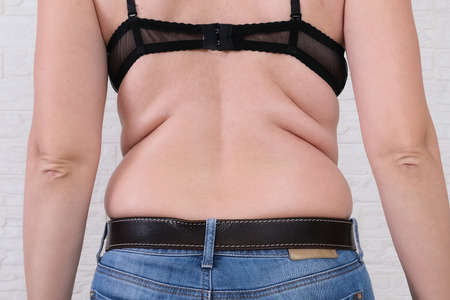 Young fat woman with excess weight, back view,flabby sides and back with folds of fat, overweighted fat body as s result of improper diet