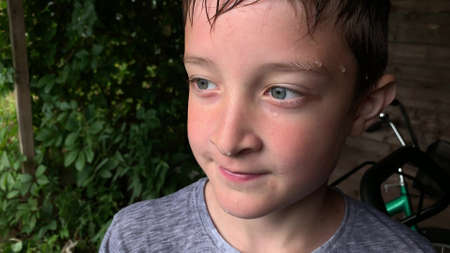 A portrait of a boy with a raindrops on a face and wet hair after downpour, bad weather and storm in summer Reklamní fotografie