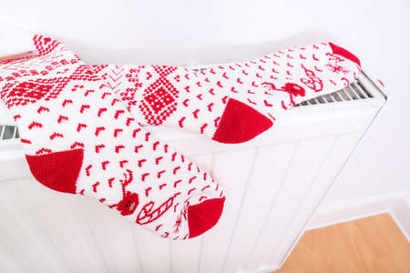 White and red christmas socks hanging on warm central heat radiator, winter holiday home mood. Reklamní fotografie