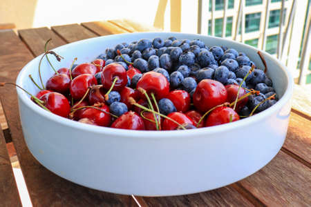 Raw juicy berries of sweet cherry and blueberry in a white ceramic dish Reklamní fotografie