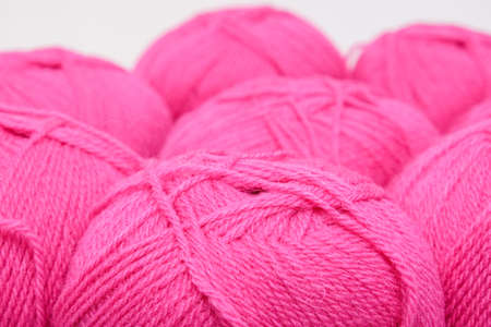 Red pink colorful skeins of yarn close up, fuchsia color woolen yarn for crochet and knitting, hobby and handmade concept Reklamní fotografie