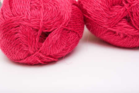 Red pink colorful skeins of yarn close up, fuchsia color woolen yarn for crochet and knitting, hobby and handmade concept, copy space.