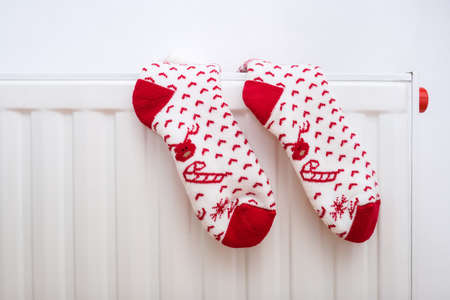 White and red christmas socks hanging on warm central heat radiator, winter holiday home mood