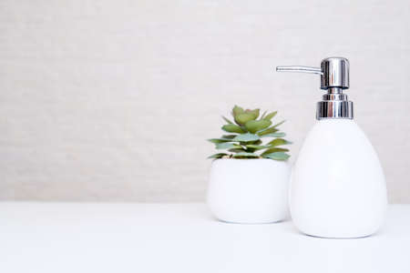 White soap dispenser and potted plant for spa, body and face care, bathroom interior in pastel colors with copy space