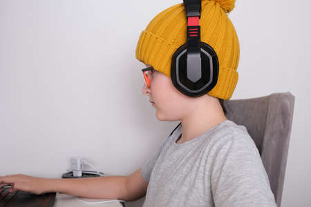 A gamer boy in a trendy knitted cap and heaphones sitting by the table and playing multiplayer computer game on laptop