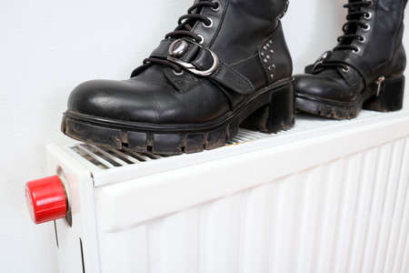 Wrong drying of footwear, a pair of dirty leather winter shoes on a hot central heating radiator Reklamní fotografie