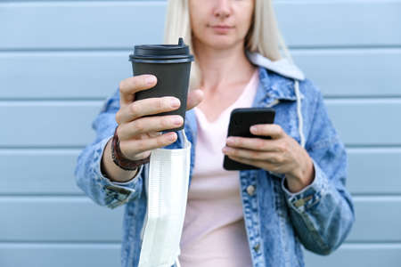 Blond unrecognizable woman with a paper takeaway cup of hot coffee and smartphone in hands, generation z with caffeine and internet addiction Reklamní fotografie