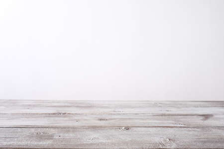 Empty wooden table top with a white backdrop behind, perspective background with copy space