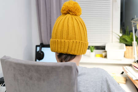 A gamer boy in a trendy knitted cap and heaphones sitting by the table and playing multiplayer computer game on laptop, back view Reklamní fotografie