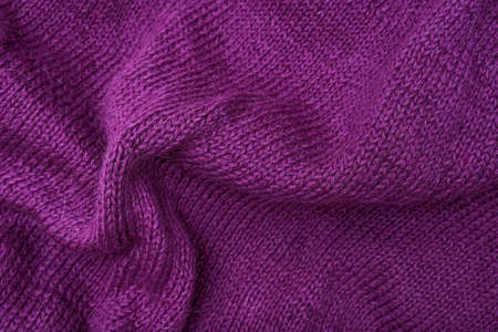 Woolen crumpled purple fabric as background close-up, violet knitted clothes, crochet and knitting Reklamní fotografie
