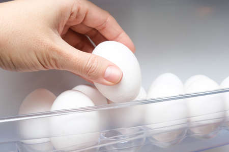 A hand taking white hen chicken egg from a shelf of a fridge, protein source for health, ingredients for fast breakfast for dieting, slimming and sports person