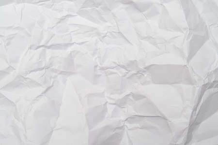 A background of sheet of white crumpled paper with wrinkles, backdrop for design and web
