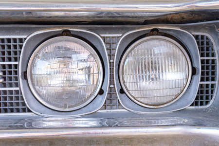 A headlight of a retro old car close up in a junk yard, changeover from old to a new modern car