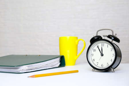 File folders, pencil, cup of coffee and alarm clock showing 5 minutes to twelve as a deadline concept for business report