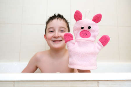 A boy in a bathroom showing funny piggy hand puppet toy washcloth close up, happy washing and shower concept