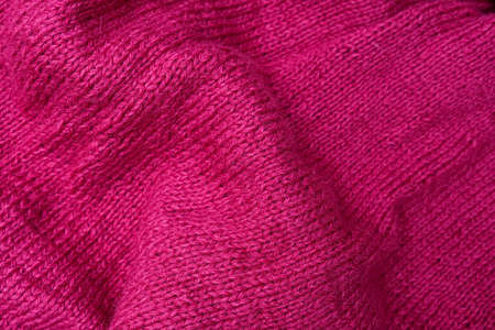 The texture of cotton folded knitted fabric, bright crumpled pink woolen knitwear textile background Imagens