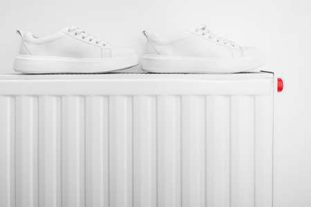 White leather sneakers drying on a central heat rasiator after getting wet or wasing and removing dirt