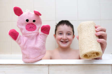 A boy with a funny face sitting in a bathtub and showing loofah and hand puppet washcloth close up