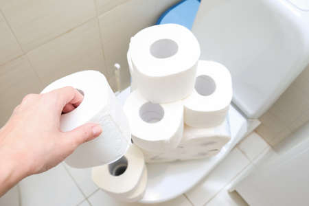 Many toilet paper rolls at home of hoarder, buying too much of hygienic means during pandemia, a hand holding a roll of toilet paper in a bathroom
