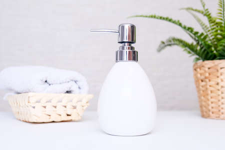 Bathroom background, toilet accessories for hand and body care, liquid soap dispenser and towels against light background Imagens