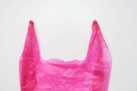 Handles of a pink plastic bag on white background Imagens