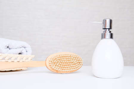 Anti cellulite dry brush massage concept, accessories for body care and self massaging, towel and cream in a bathroom with copy space