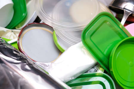 A lot of plastic waste in a kitchen drawer, plastic containers and kitchenware in mess, recycling concept Imagens