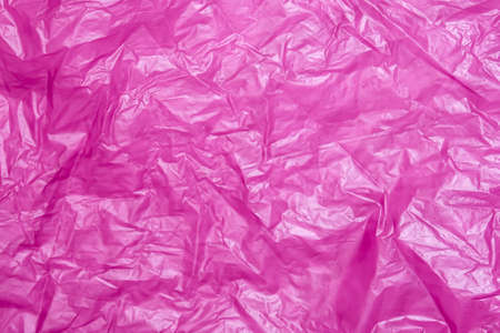 Crumpled red lilac plastic bag abstract texture background surface
