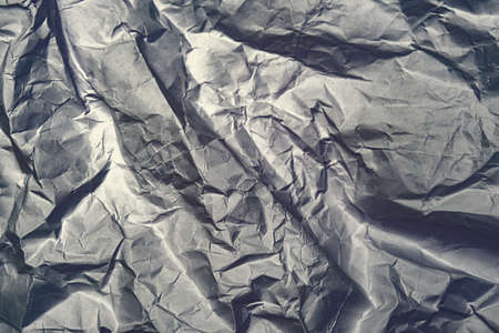 Gray crumpled shiny abstract paper background Imagens