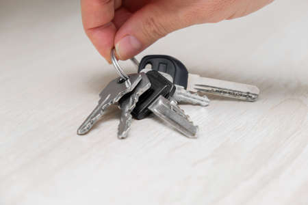 Unrecognizable person holding up a keys at home, leaving home and taking keys, home security concept