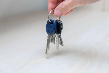 Hand holding up a keys at home, leaving home and taking keys from table or shelf, home security concept Imagens
