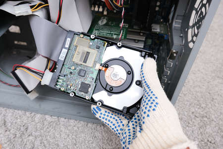 Moscow, Russia - September 10, 2020: Engineer changing the hard drive of an office computer, repairing and fixing broken hard disk for data recovery