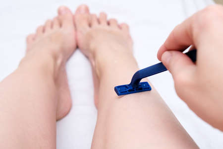 Woman shaving legs with a blue disposable plastic razor close up, unwanted hair removing