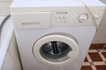 An old broken washing machine in a bathroom need to be recycled and replaced
