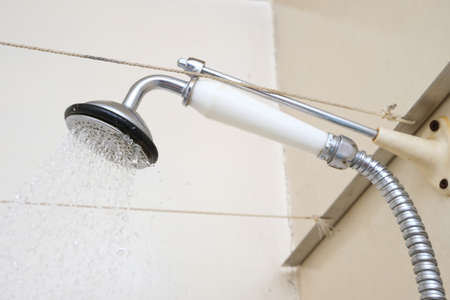 Water flowing from an old shower head with ceramic handle with limescale needed to be replaced or decalcified Imagens
