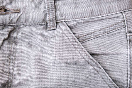 Shabby gray jeans background with fore pocket, denim fashion background.