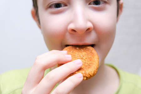 A portrait of a preteen boy eating tasty cookie, snacking concept.