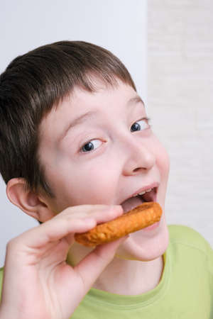 A portrait of a preteen boy eating tasty cookie, snacking concept