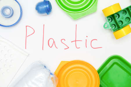 Sign plastic surrounded with many pet plastic objects, things bottles toys caps that can be recycled in order to save nature and protect environment