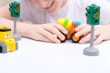 A boy playing toy cars on a white table.