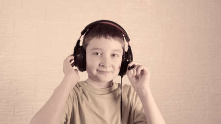 A boy in headphones listening to music, he shaking and nodding his head in time to the music, vintage toned and stylized