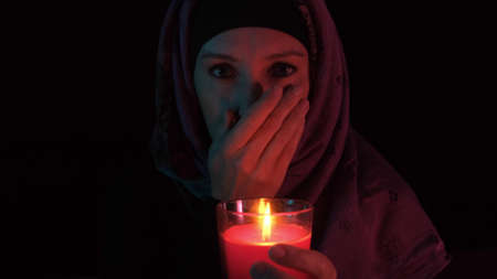 A woman in grief holding a burning red candle and covering her mouth with palm Reklamní fotografie