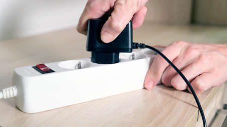 A hand inserting a plug into electrical power strip close up, charging devices concept