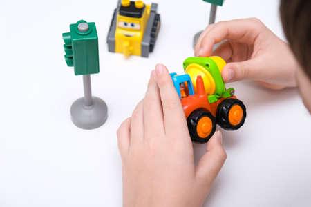 A boy playing toy cars on a white table Reklamní fotografie