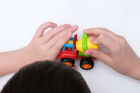 A boy playing toy cars on a white table 스톡 콘텐츠